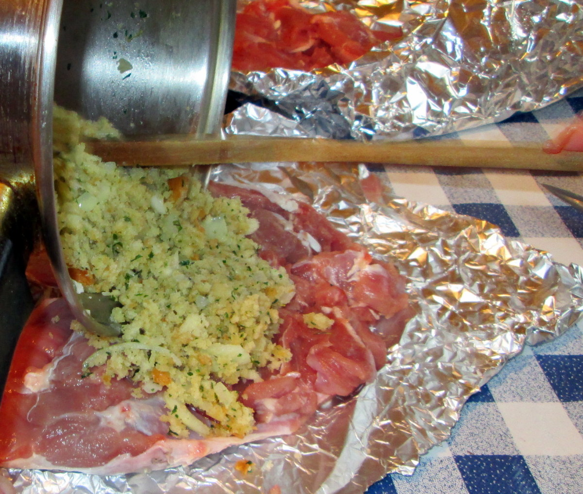 Adding the stuffing to the turkey meat on the tinfoil.