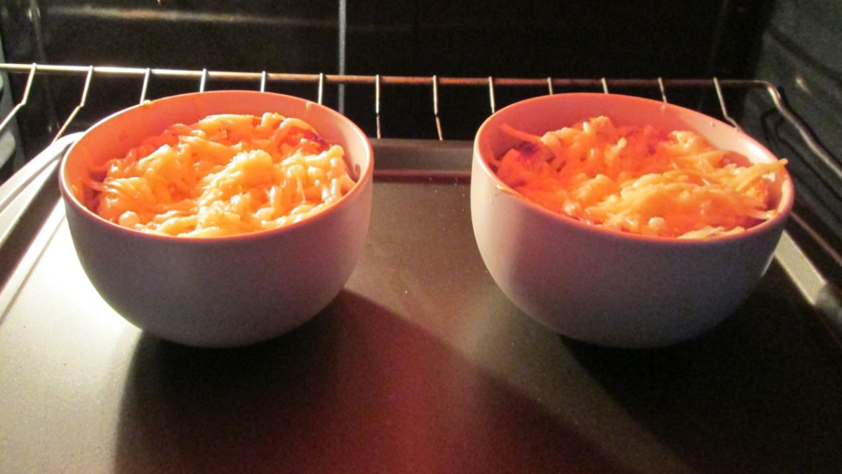 Two bowls of French Onion Soup baking in an oven.