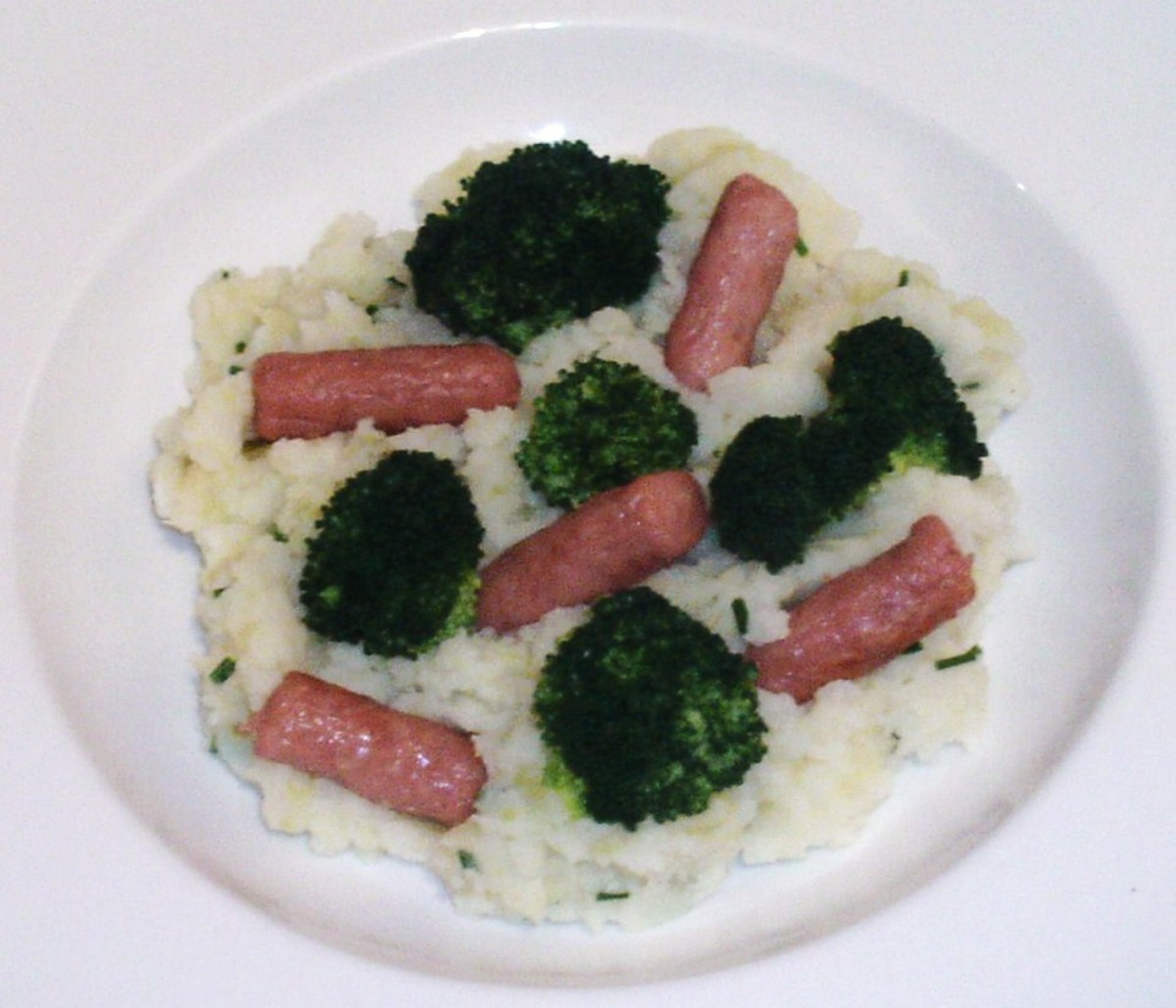 Simply cooked broccoli is served with mini sausages and mashed potato and broccoli stalk