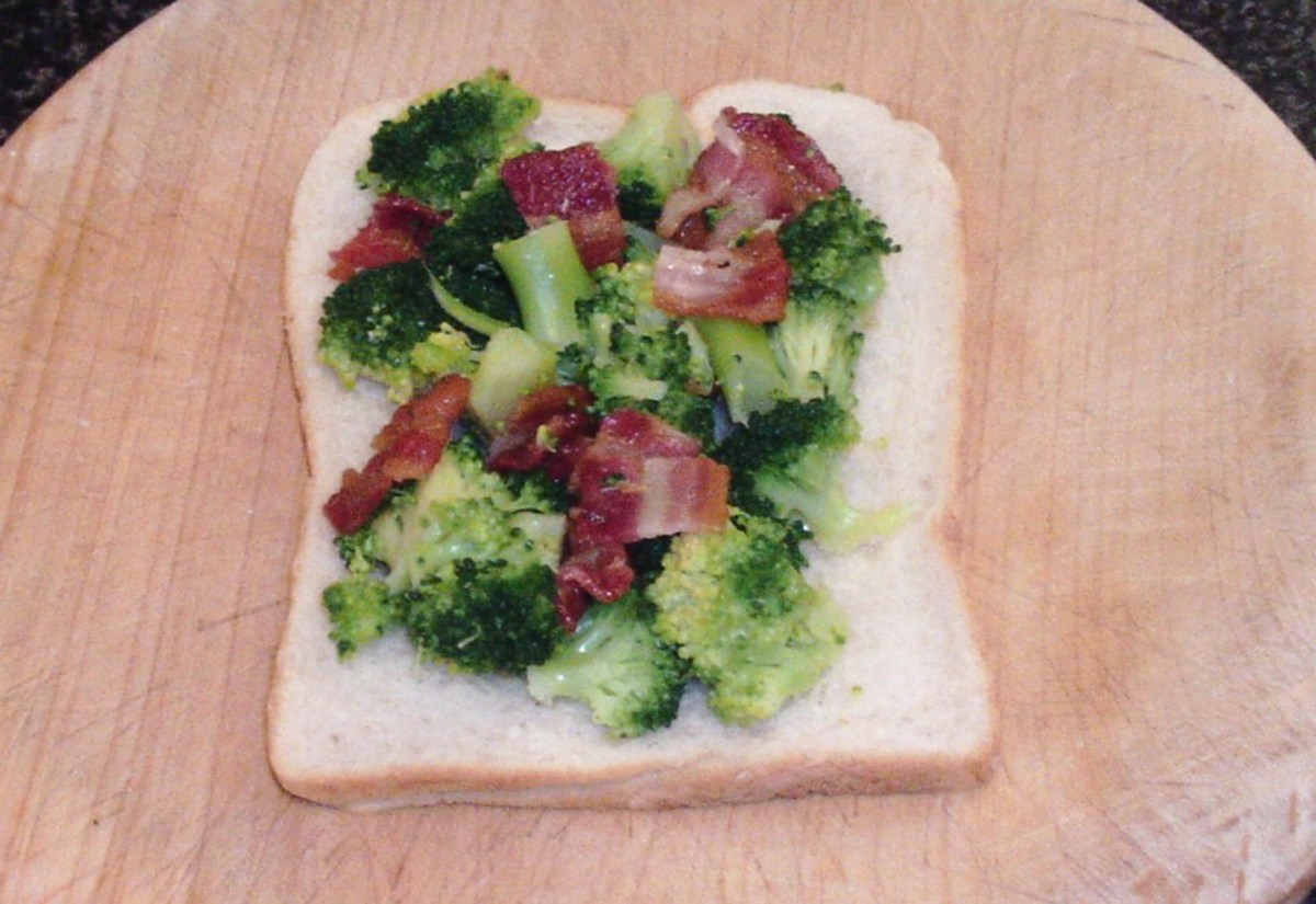 Bacon and broccoli are laid on uintoasted side of bread