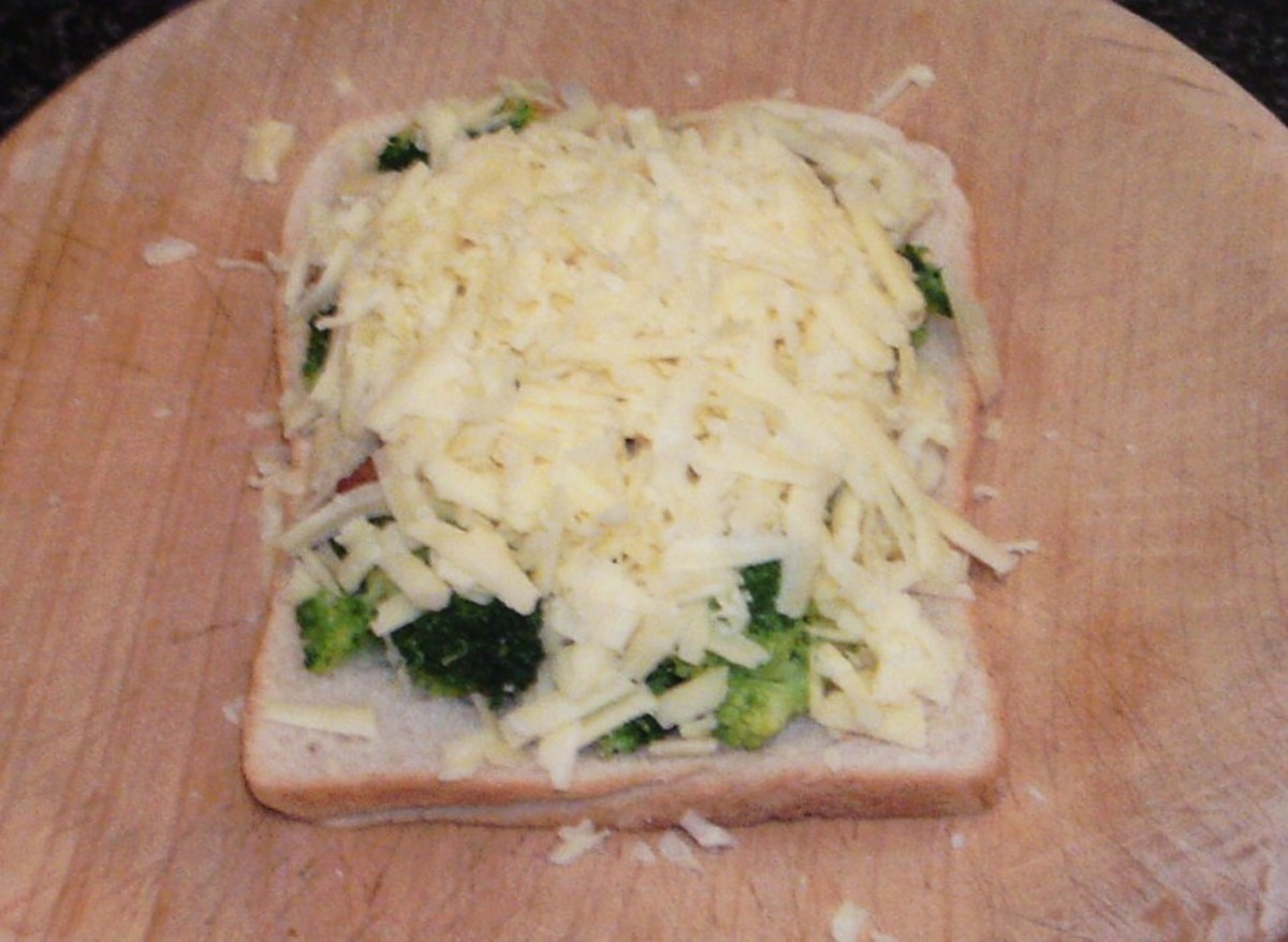 Cheese is carefully arranged over broccoli and bacon
