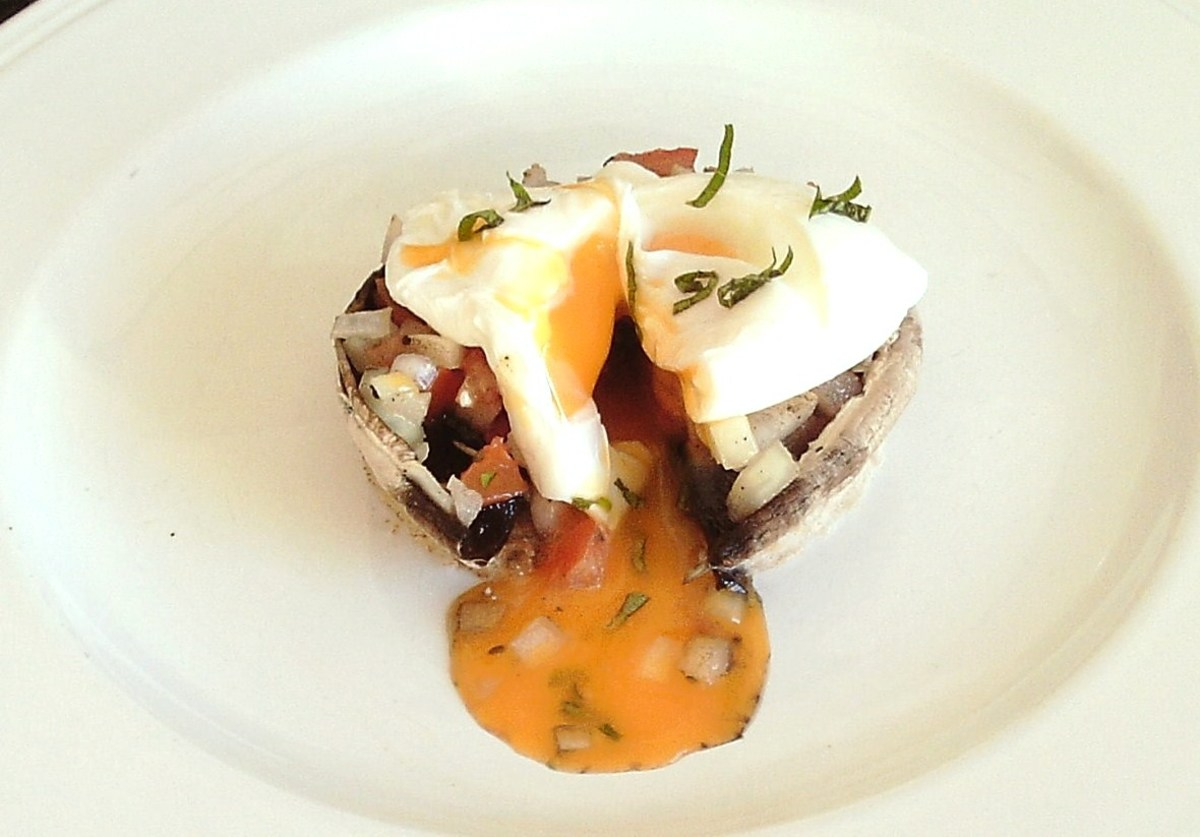 Egg poached to perfection is sat on top of a tomato and onion stuffed mushroom on toast