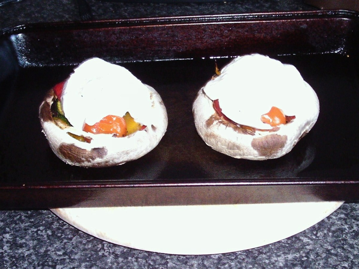Mozzarella slices laid on roasted stuffed mushrooms