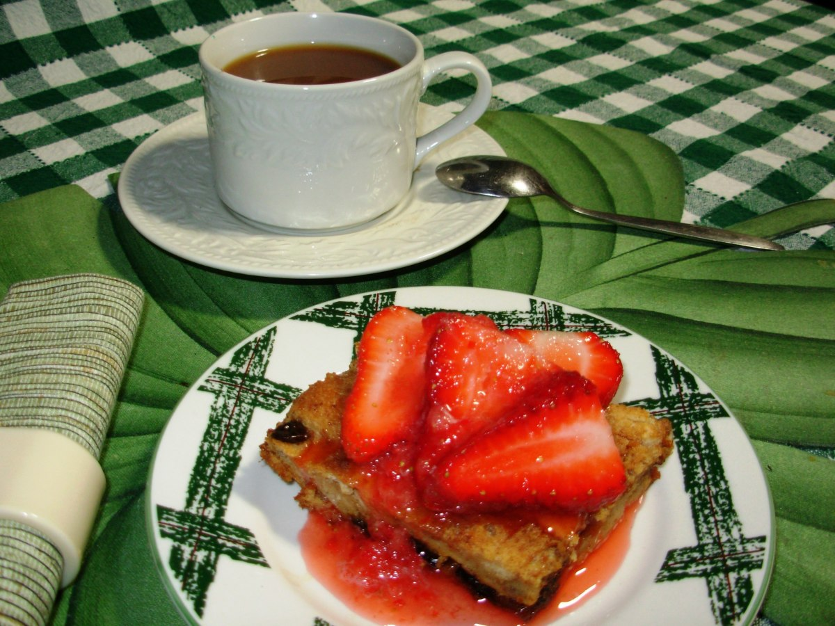 A slab of bread pudding topped with fresh strawberry topping.