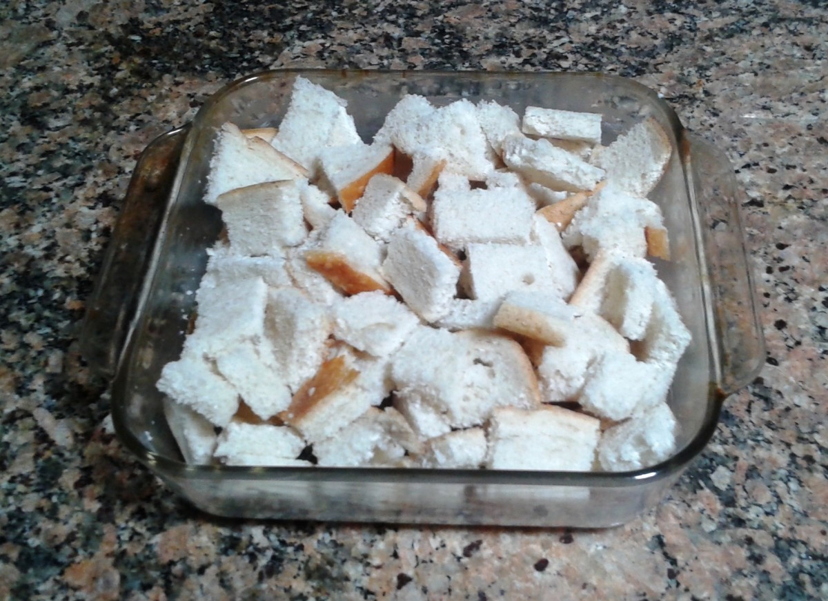The cut-up bread squares are placed in a buttered baking pan.