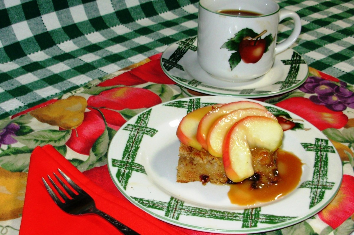 A slab of bread pudding topped with sauted apple slices and drizzled with caramel sauce.