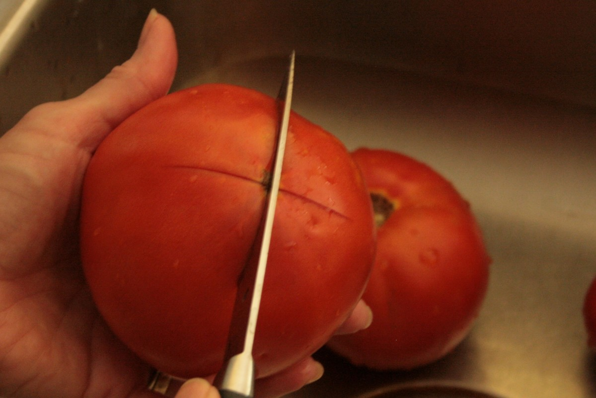 Score the bottom of the tomato prior to blanching so that the peel will easily pull away.