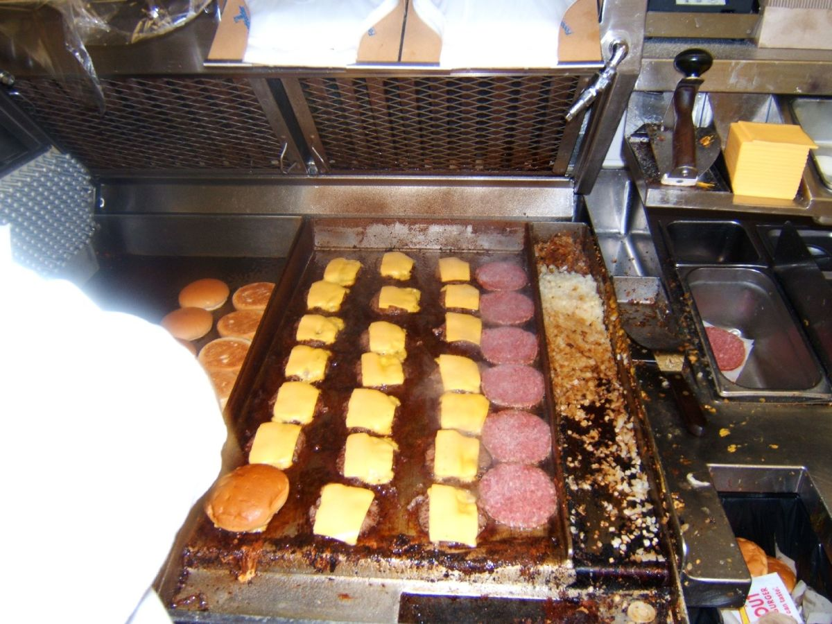 I'm not sure how an associate got away with taking this photo, but here's the grill.  Looks like the cook is having a busy day; that's a lot of cheeseburgers and double-doubles!  You can also see grilled onions being cooked on the right.