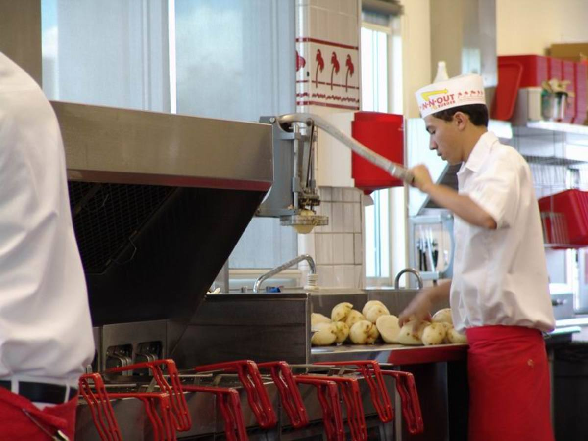 An In-N-Out associate dicing potatoes to make fries.  In the back, other associates are probably cleaning and peeling potatoes which will be diced later.