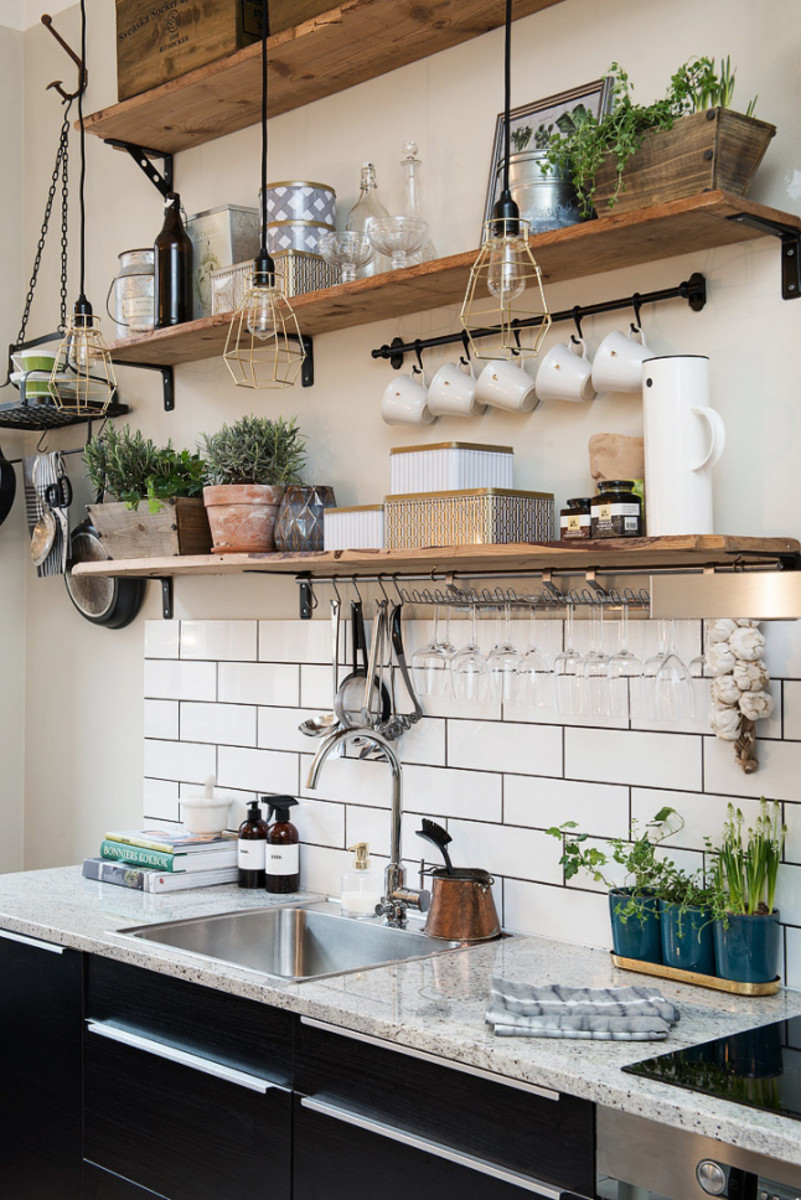 This small kitchen makes nice use of a mix of open shelves, hooks, and hanging baskets to organize kitchen items without feeling cluttered.