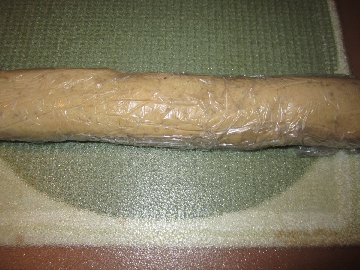 Pecan sandie log wrapped in plastic wrap ready for the refrigerator.
