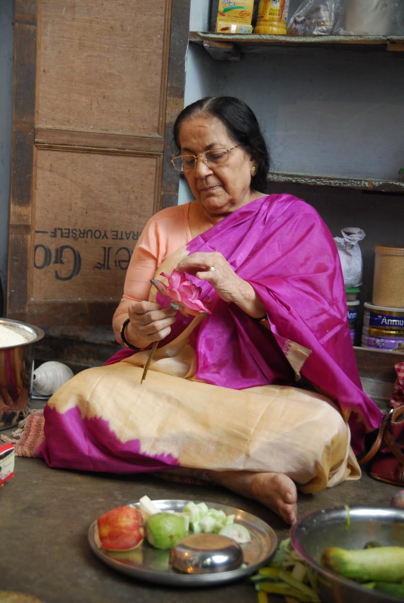 Grandma opening a lotus to offer to Goddess Durga.
