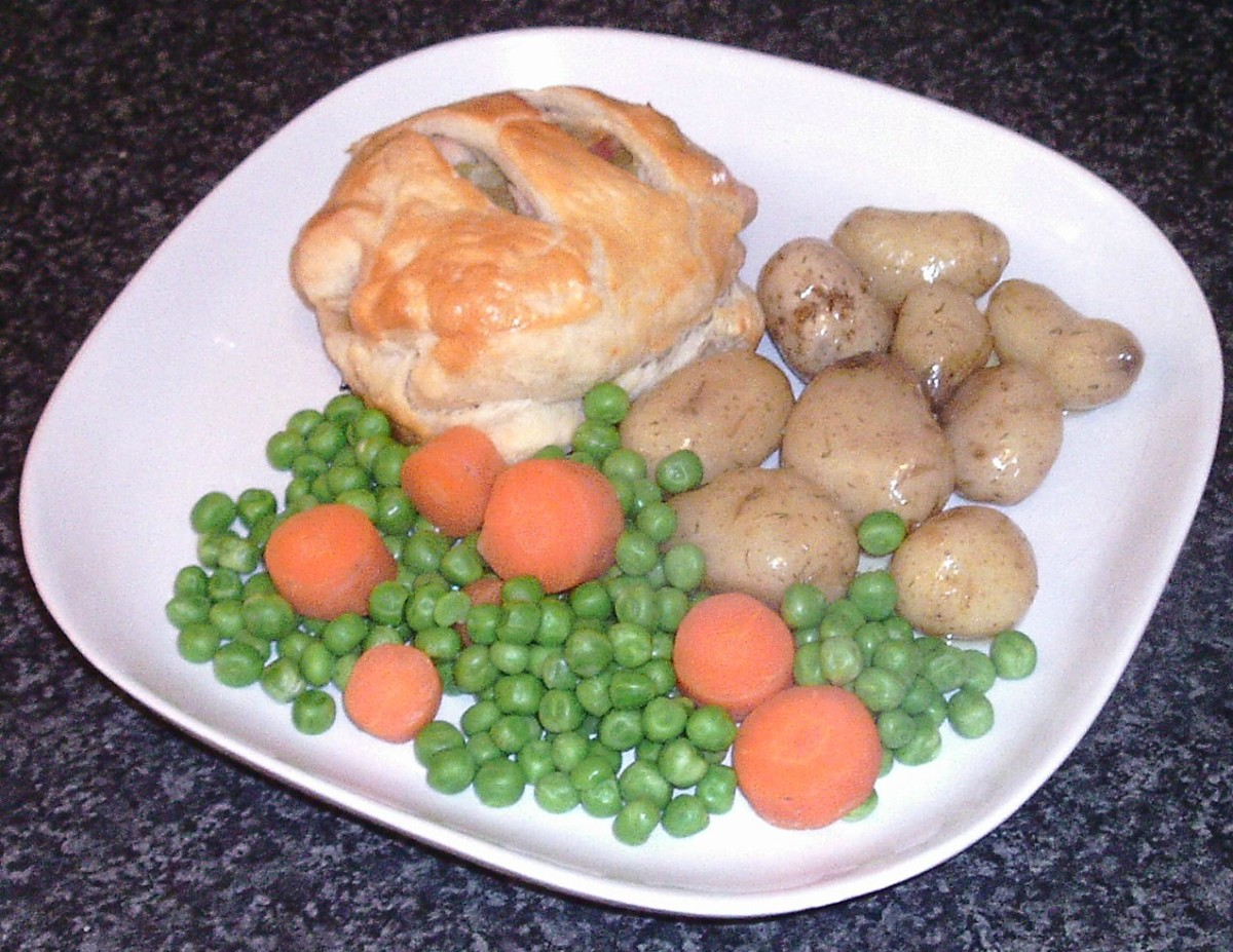 Leek and bacon stuffed chicken thigh in puff pastry with boiled new potatoes, peas and carrots