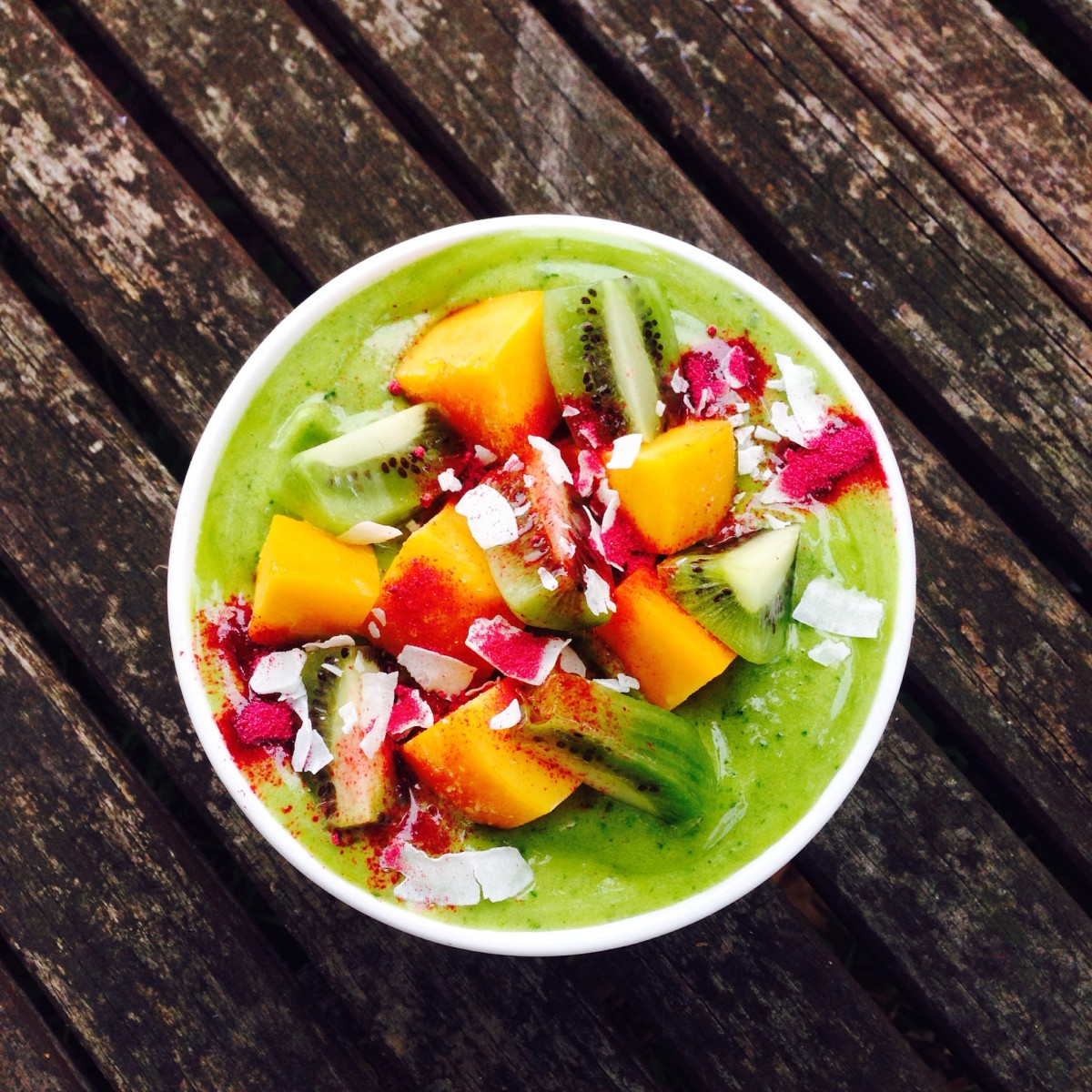 Green smoothie bowl topped with fresh fruit and coconut.