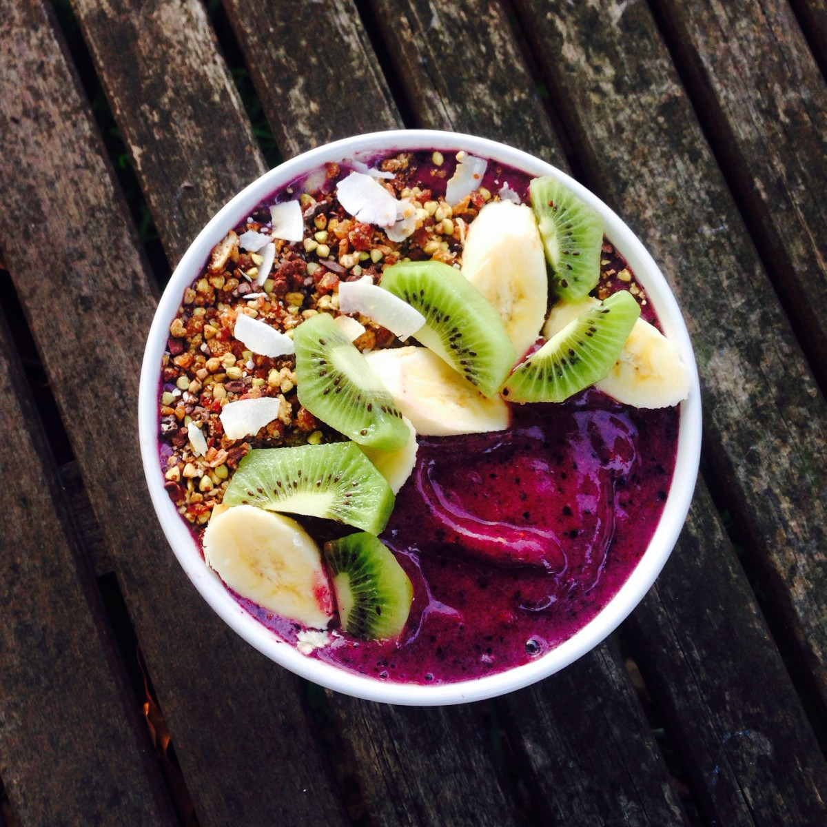 Acai smoothie bowl topped with fruit and granola.