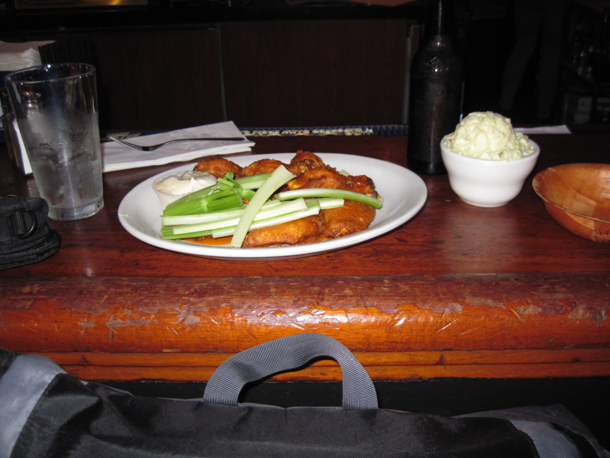 A plate of Buffalo wings with celery and dip.