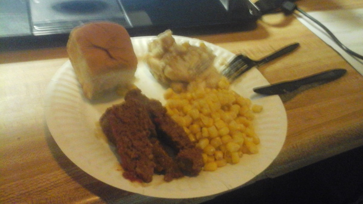 a dinner plate with potatoes and gravy, corn and a sweet Hawaiian roll