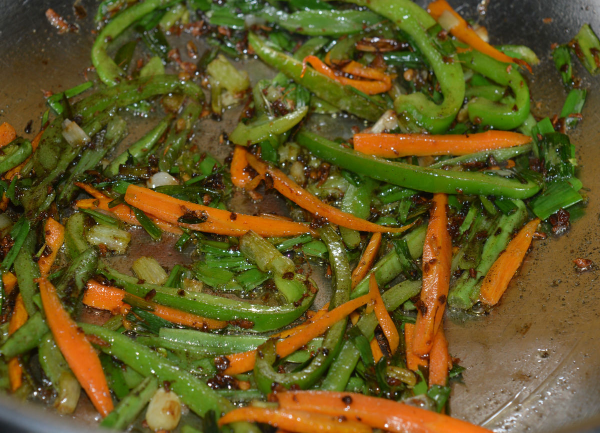 Pan-frying the vegetables.