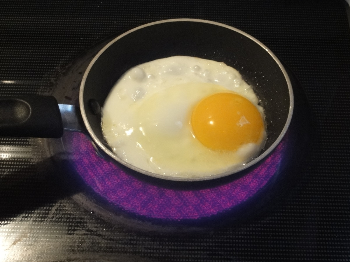An egg frying in a single-serve frying pan.
