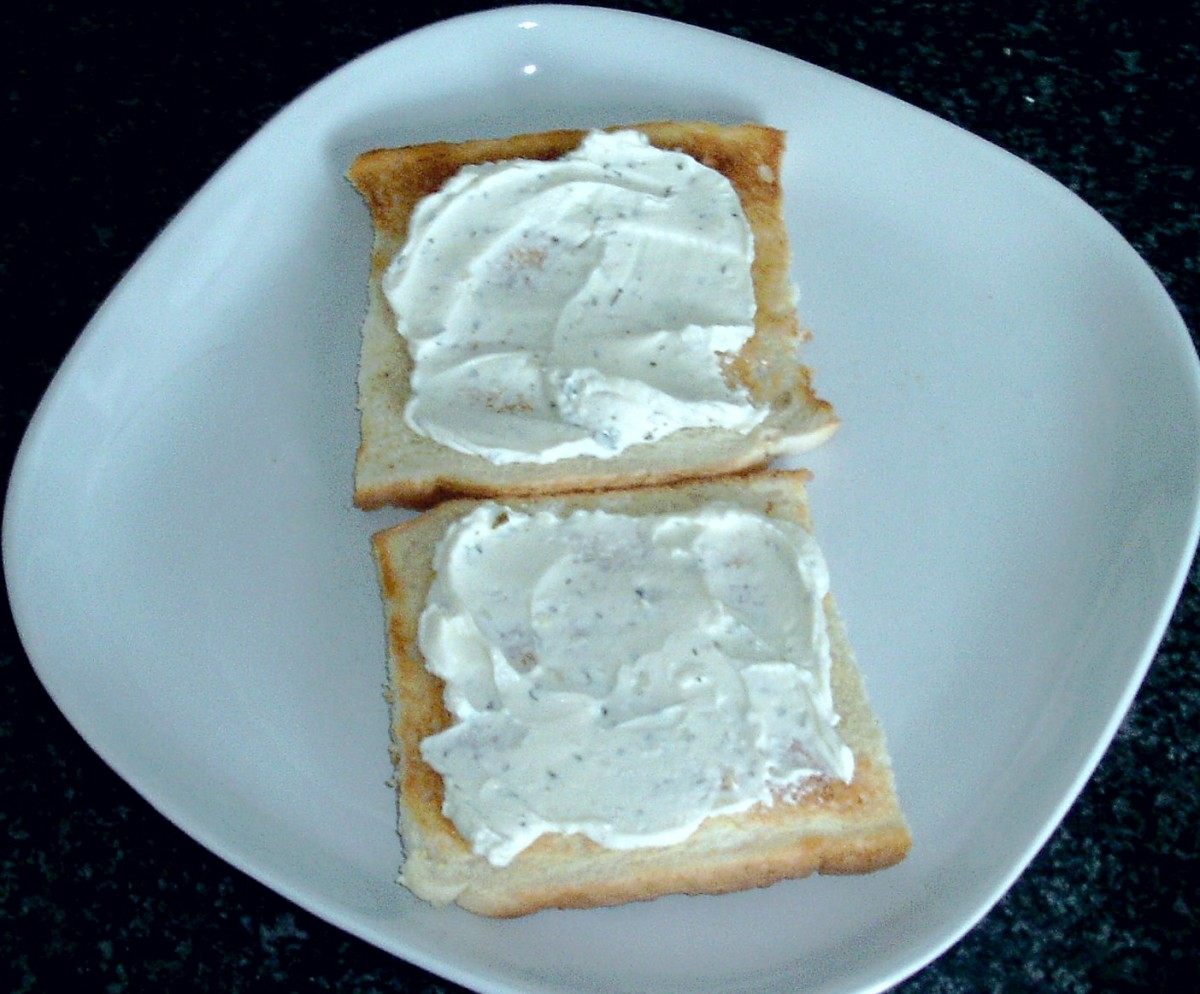 Cream cheese is spread on toast