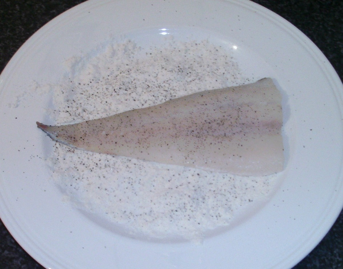 Cod is patted in seasoned flour