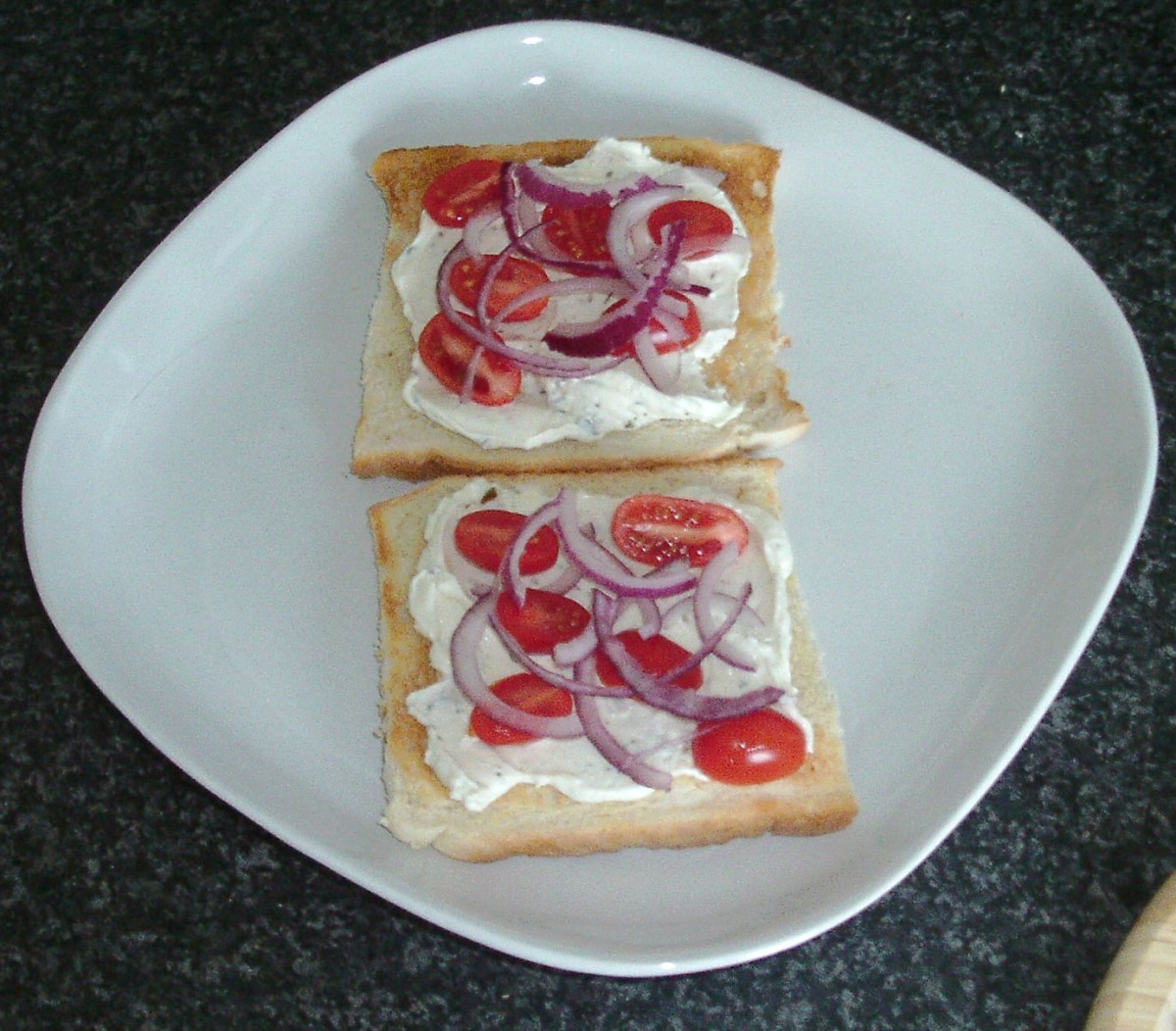 Tomatoes and red onion are scattered over cream cheese
