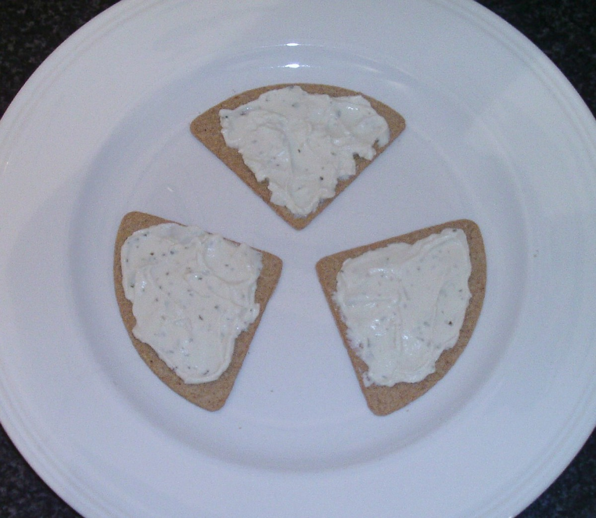Cream cheese is spread on oatcakes