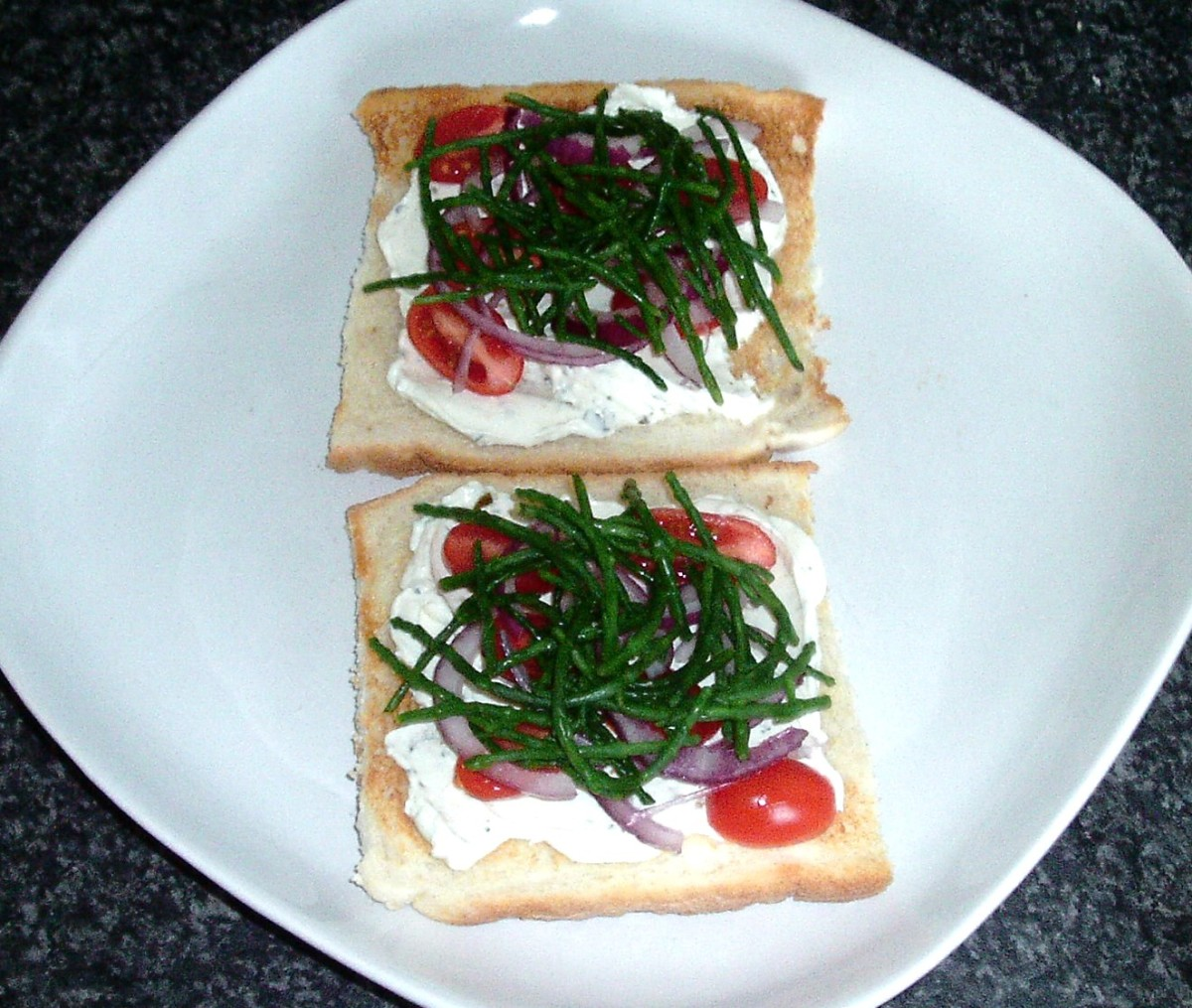 Cream cheese is spread on toast and topped with tomatoes, red onion and samphire