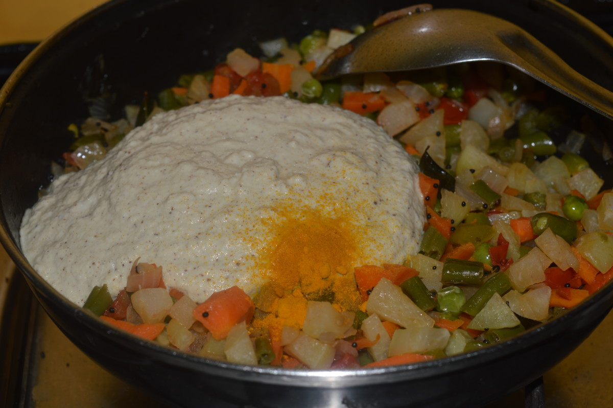 Adding the gravy to the vegetables.