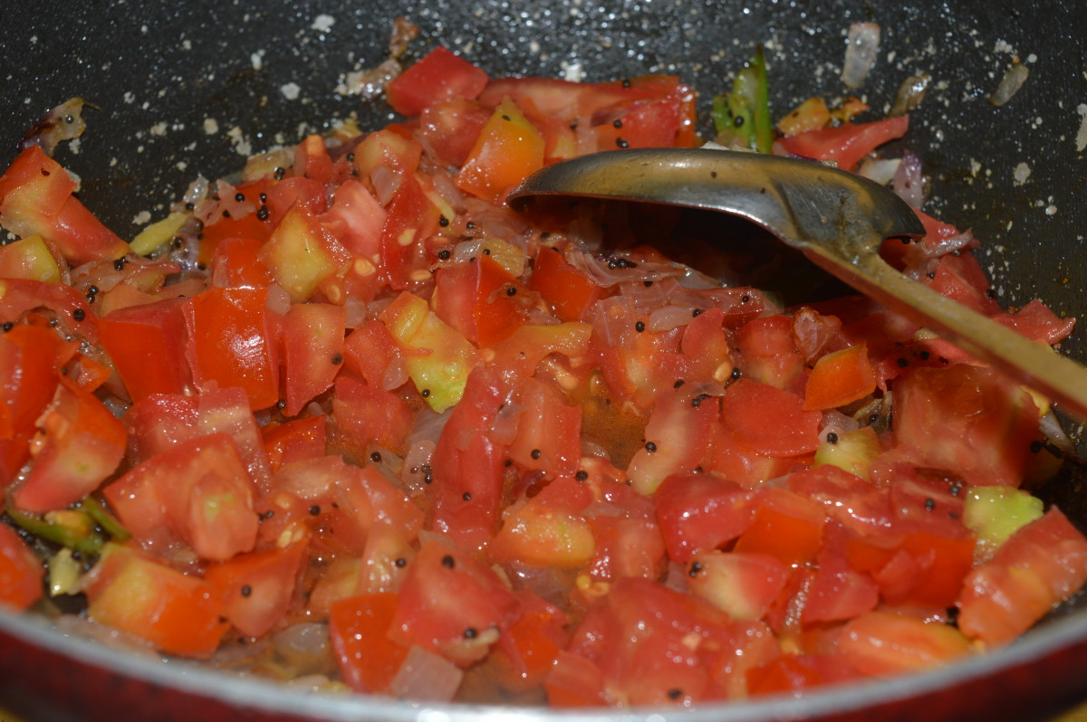 Sauteing the tomato with spices and other vegetables.