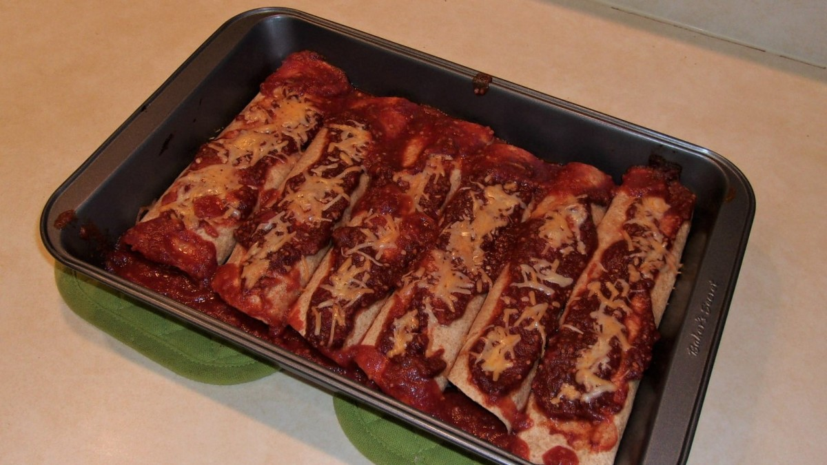Covering the enchiladas with sauce and vegan cheese.