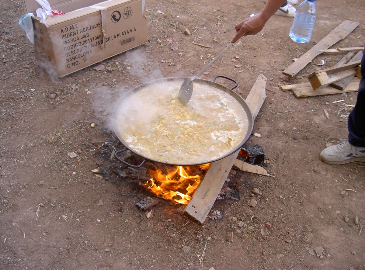 A paella pan over an open flame