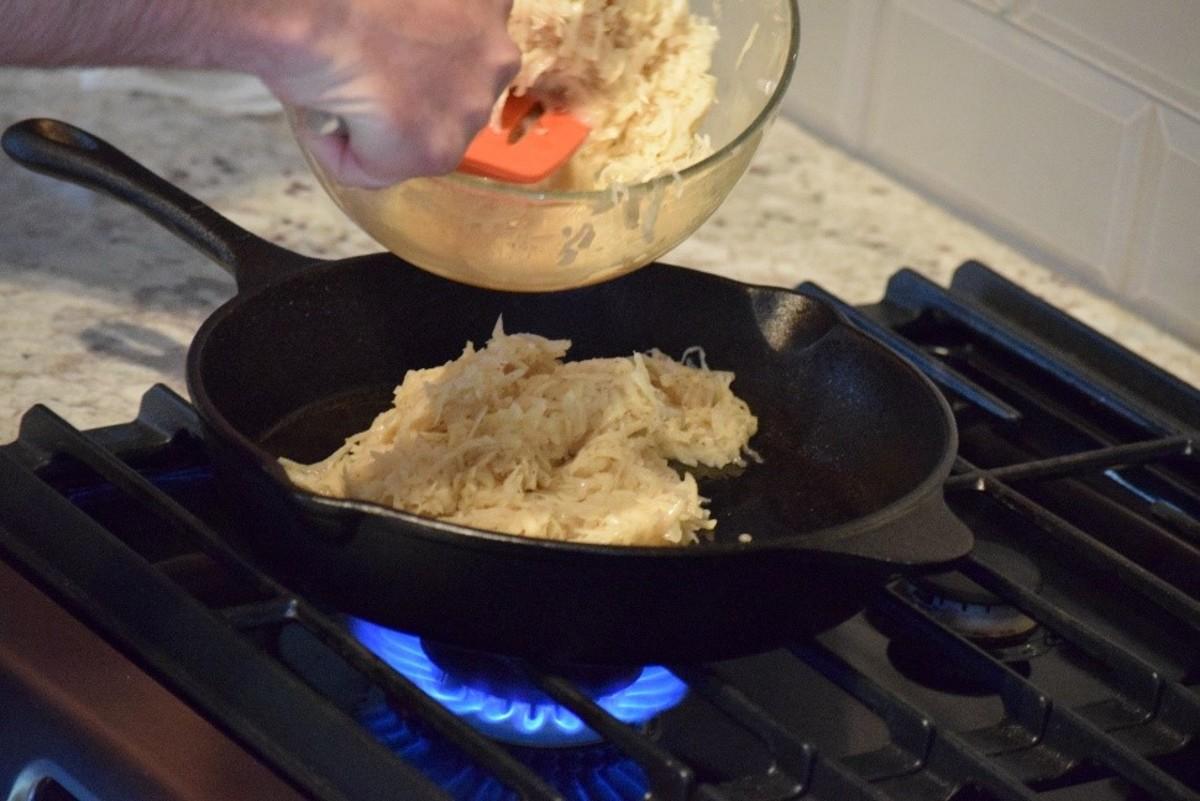 Adding the potato mixture to the pan.
