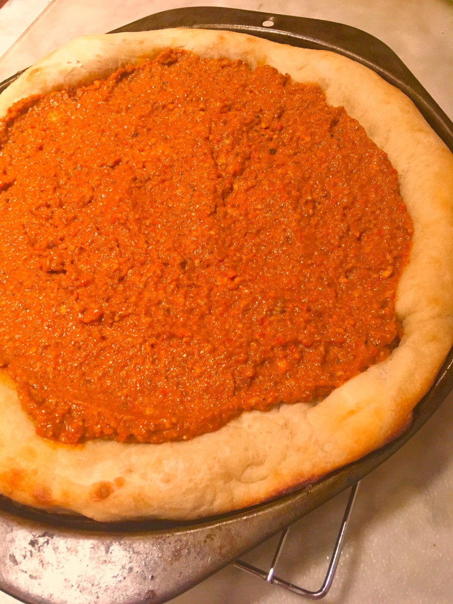 Homemade romesco sauce on a par-baked pizza crust