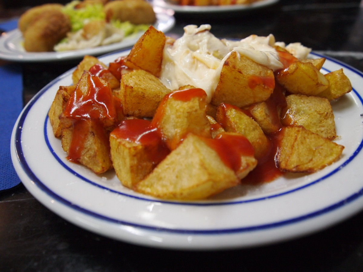 Patatas bravas served with tomato ketchup and aioli on top.
