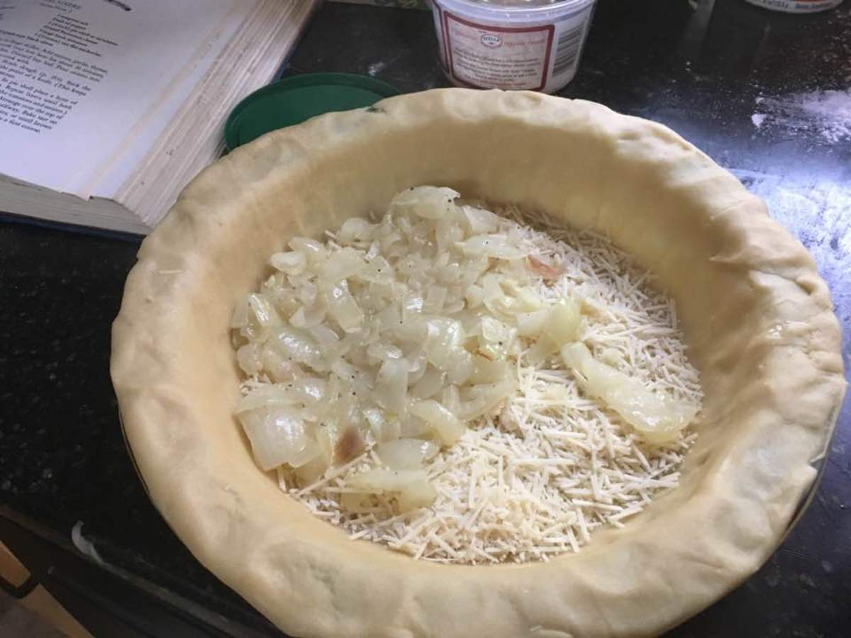 Laying onions and cheese in the pizza shell.