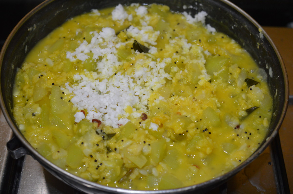 Step six: Bottle gourd and mung bean almost  cooked. Add grated coconut, turmeric powder, jaggery powder, and remaining salt. Mix well.