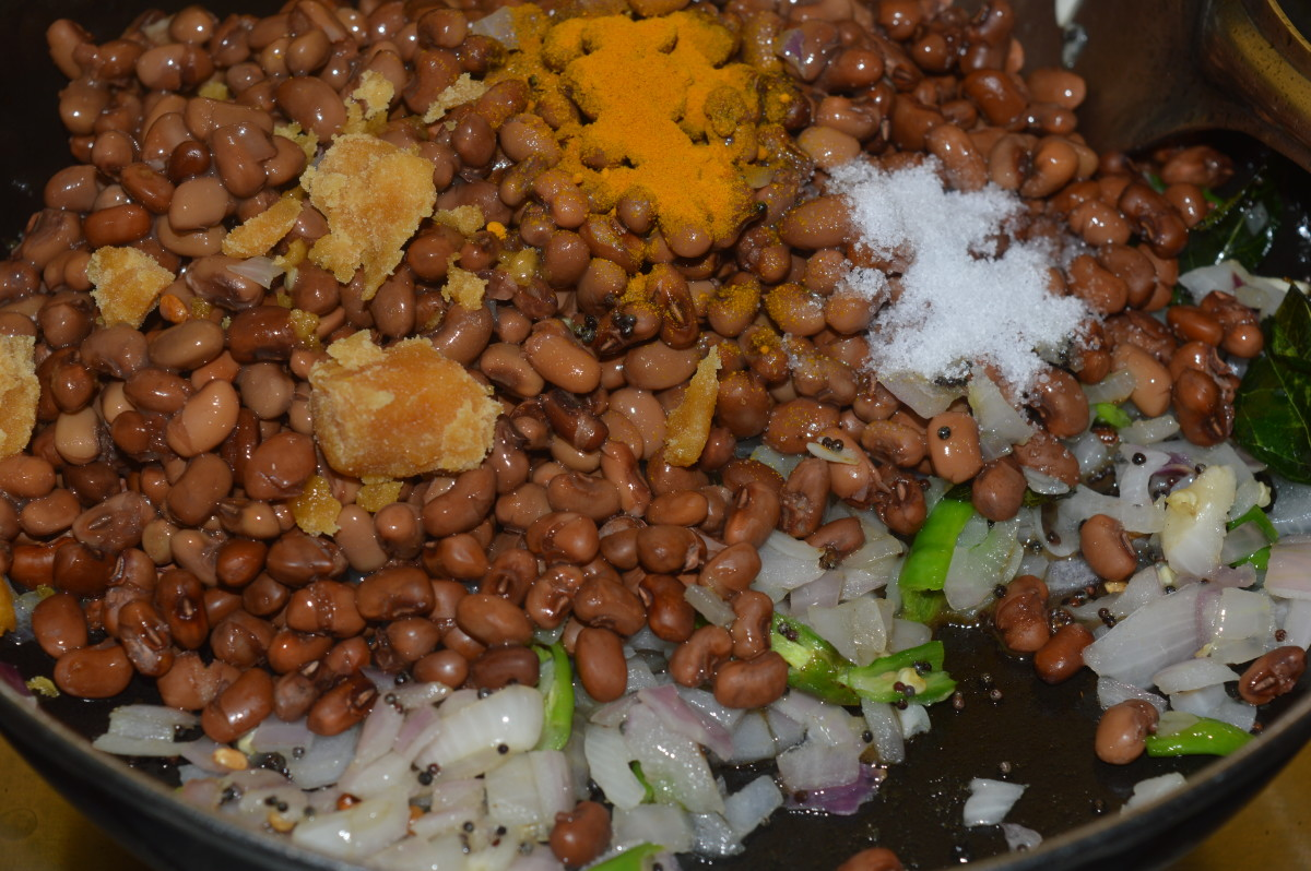 Step five: Add cooked beans, turmeric powder, jaggery powder, and salt. Mix well. Cook for 2 minutes.