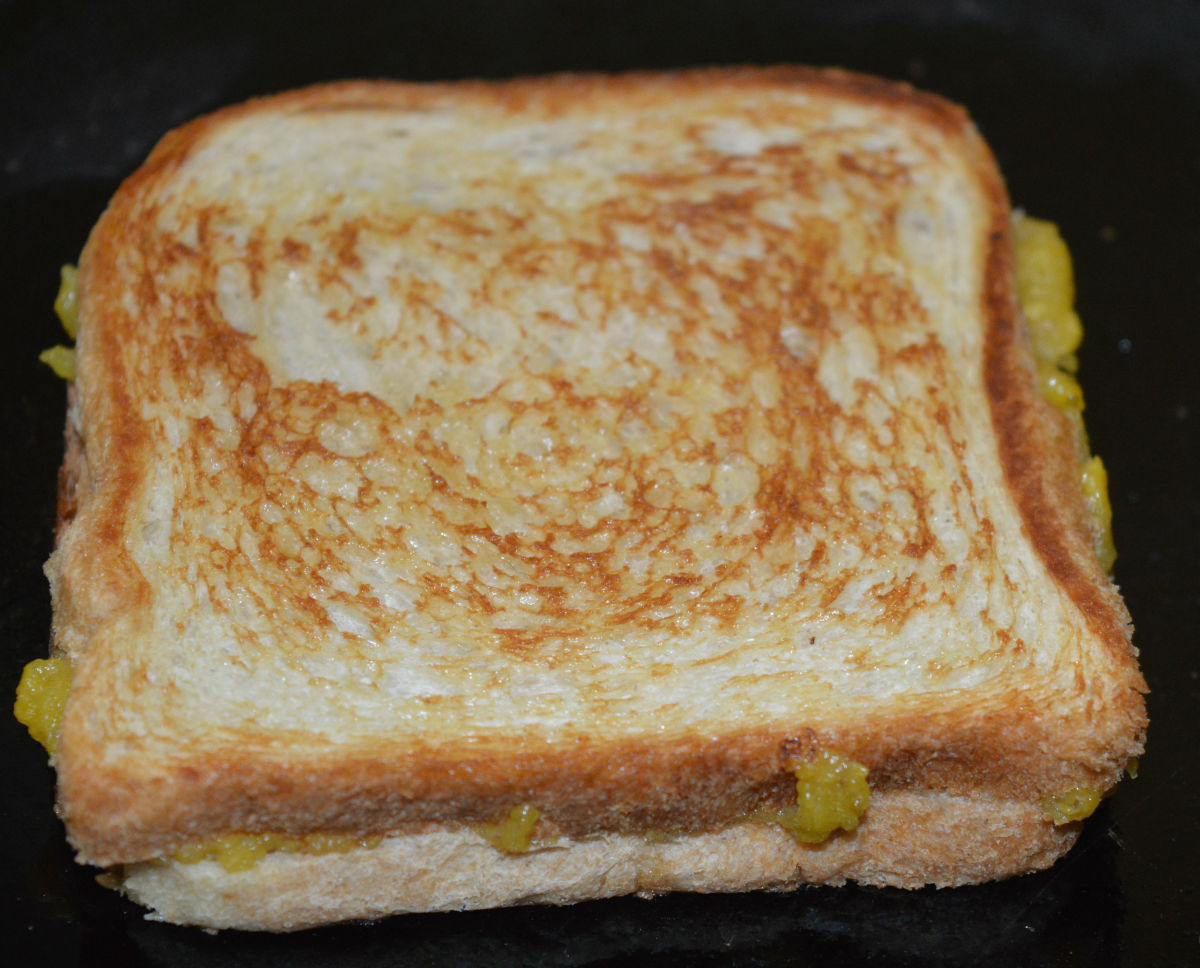 Step eight: Sprinkle some ghee or butter on the pan. Roast the sandwich till golden brown on both sides.