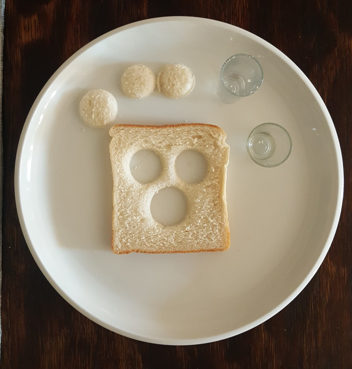 Cut out 3 circles in the shape of eyes and a nose in a slice of bread.