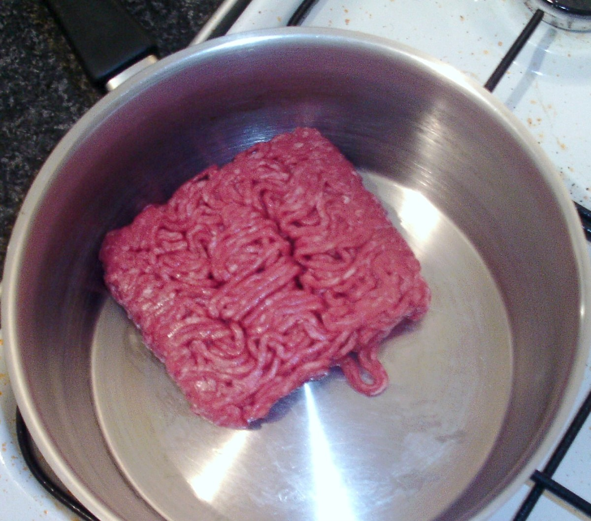 Beef is added to a dry pot for browning