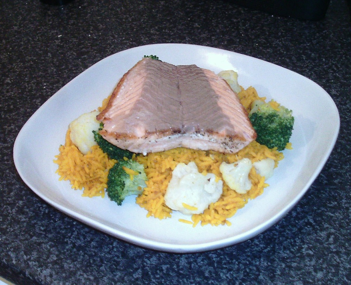 Pan fried salmon fillet is served on a bed of turmeric rice with broccoli and cauliflower