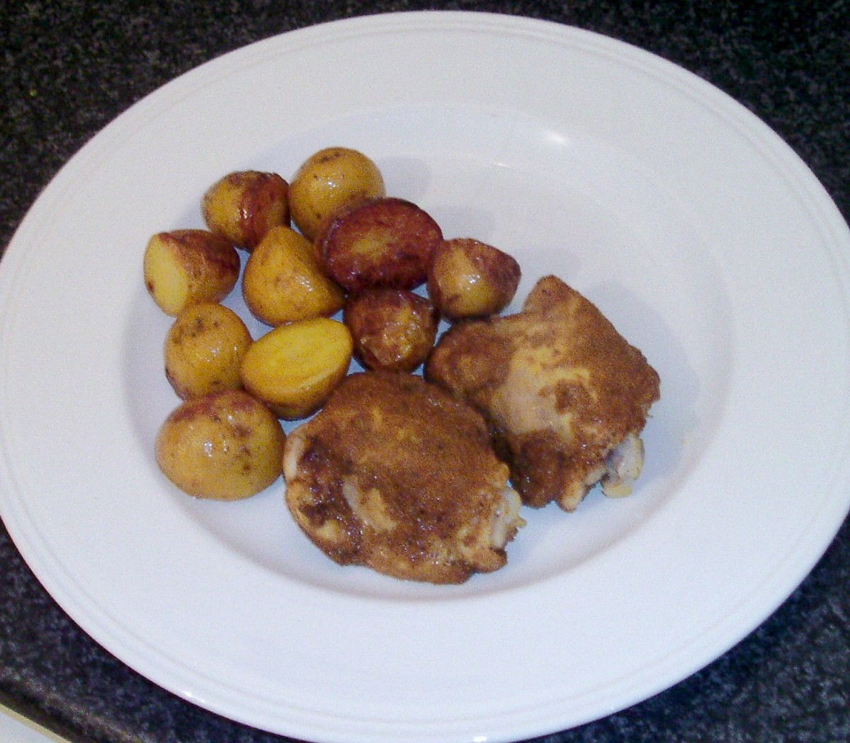Plated chicken thighs and roast potatoes