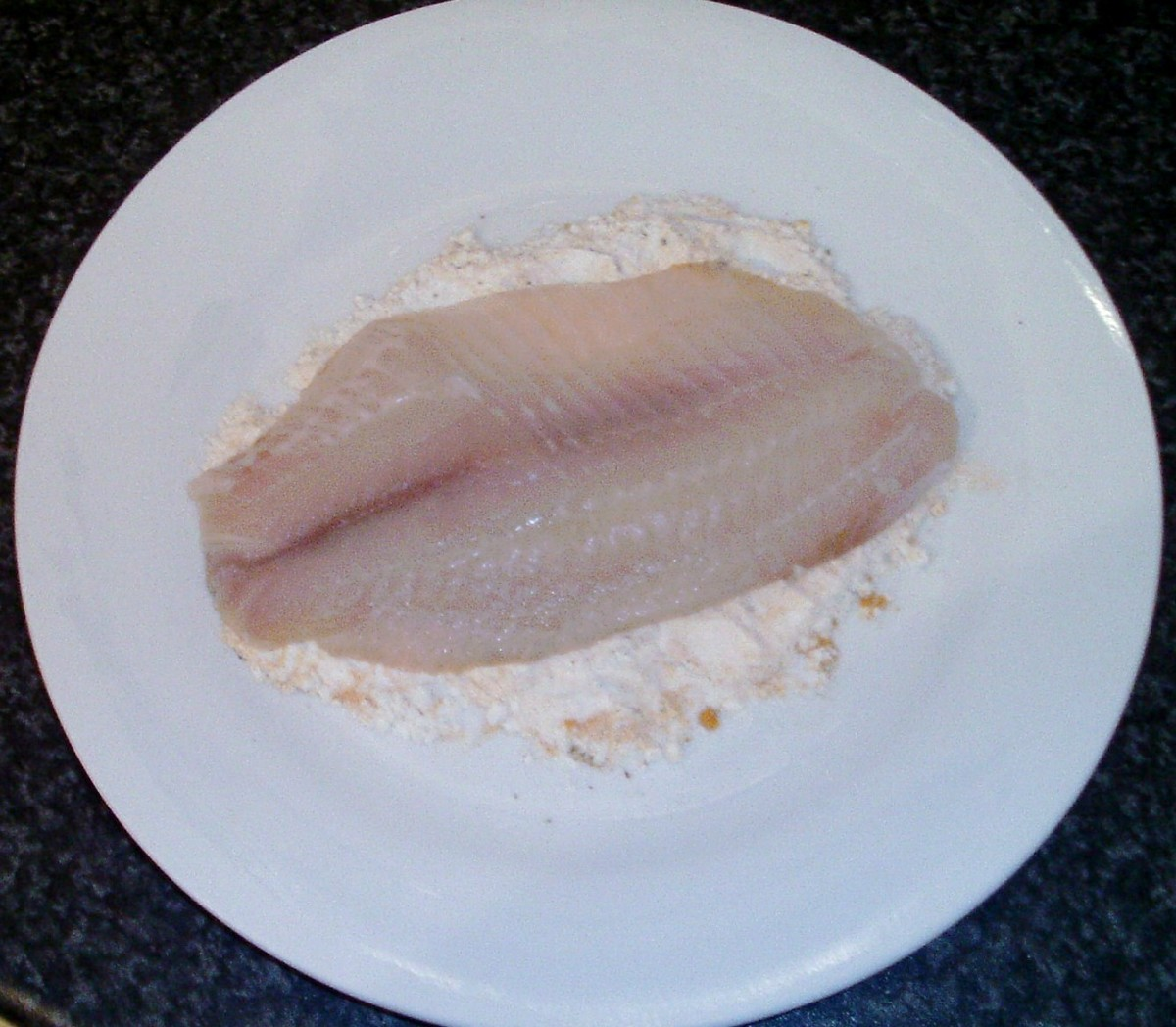 Tilapia fillet is patted in seasoned flour