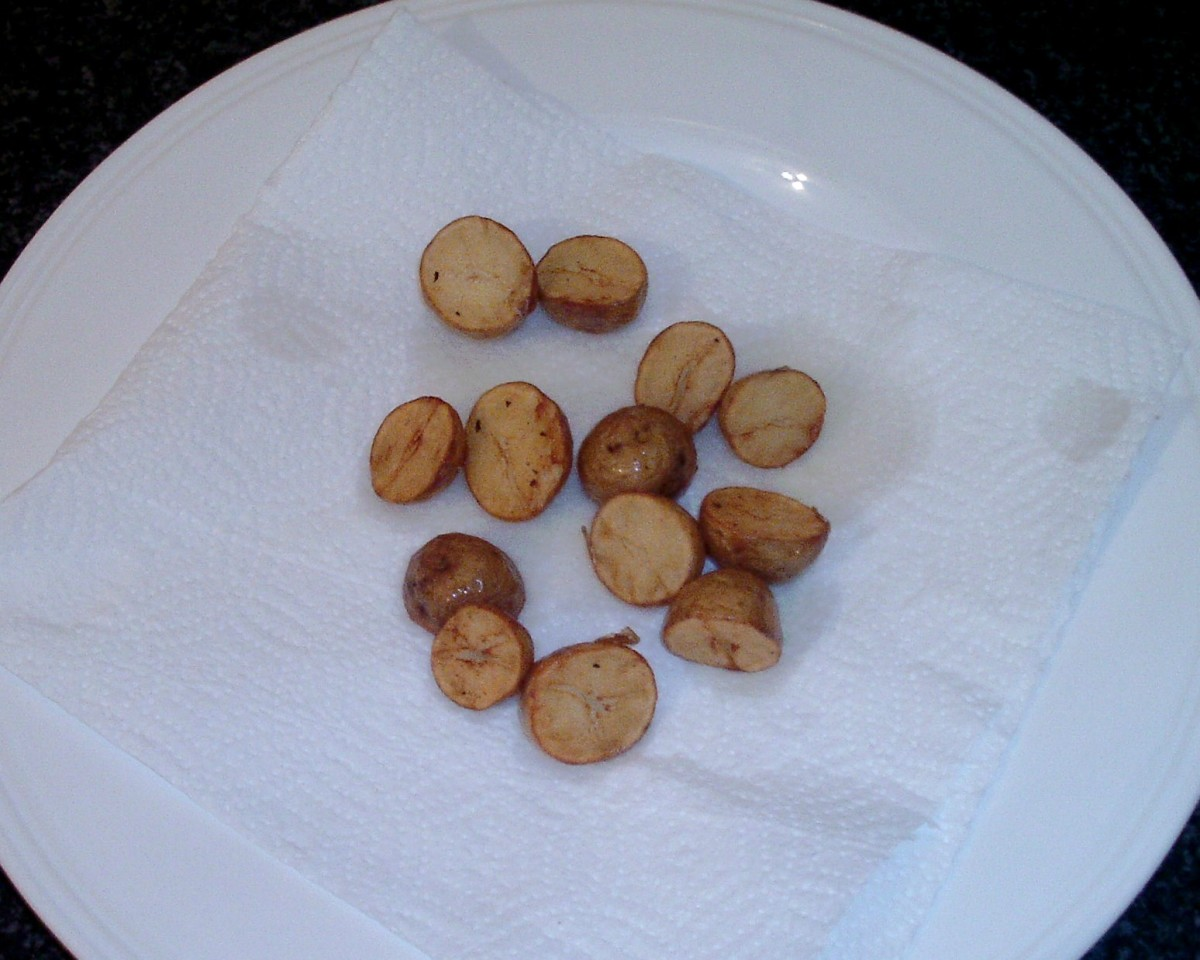 Fried potatoes are drained on kitchen paper