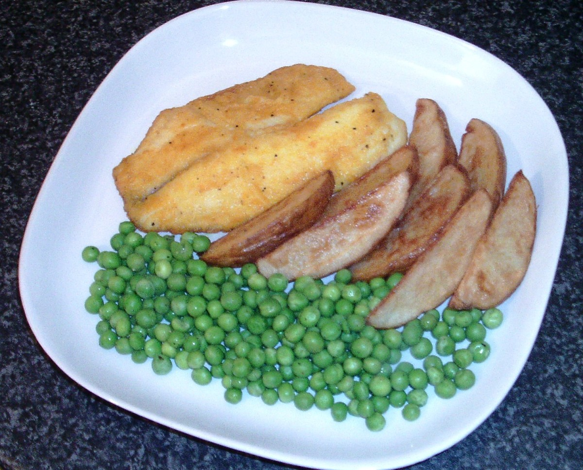 Pan fried turmeric spiced tilapia fillet with deep fried potato wedges and peas