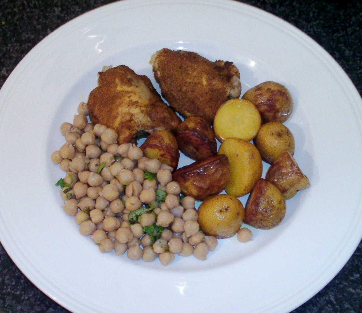 Turmeric spiced baked chicken thighs with roast potatoes and chickpeas