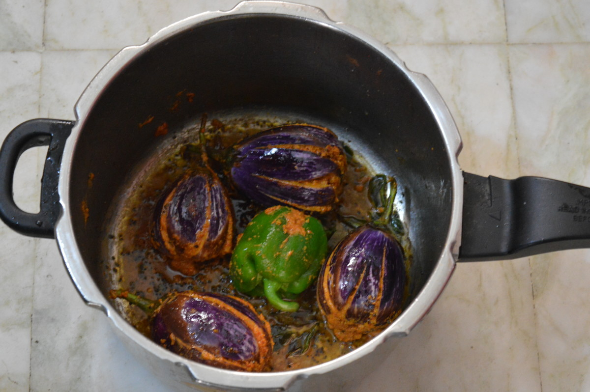 Step five: Heat oil in a cooker base or in a heavy bottom pan. Place stuffed brinjal/eggplant one near the other. Cook on low fire for 3 minutes, turninig them occasionally to ensure uniform cooking. Add the remaining paste and pour a cup of water.