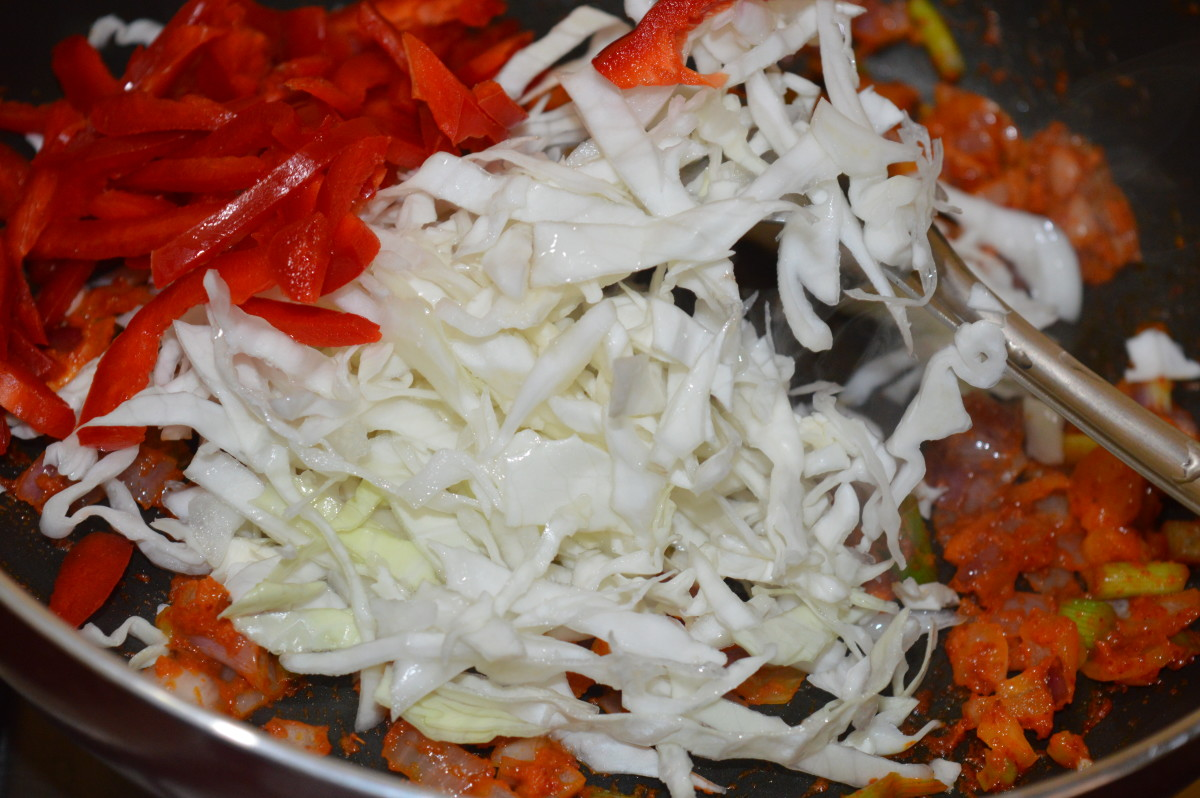 Step five: Throw in shredded cabbage, and chopped red capsicum. Add salt and mix. Keep the heat medium high.