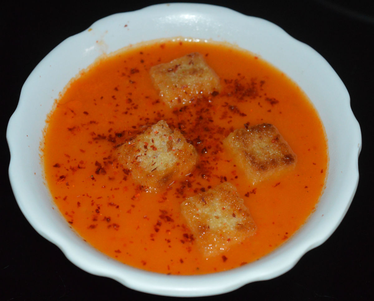 Step twelve: Tomato and sweet pepper soup is ready. Pour it equally into four bowls. Garnish with breadcrumbs and Kashmiri red chili powder. Enjoy sipping this delicious hot soup!